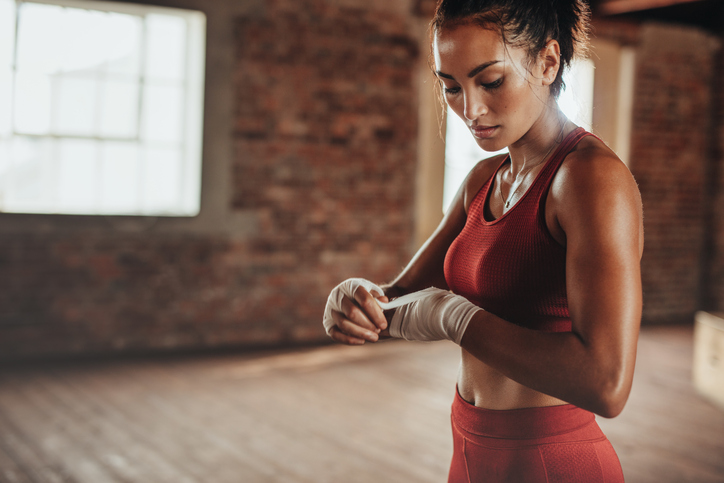 Healthy young female boxer wearing strap on wrist. Muscular built woman getting ready for boxing exercise at fitness studio.