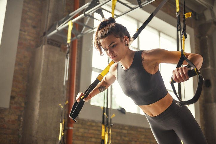 Perfect push-up. Side view of young athletic woman with perfect body in sportswear doing push ups with trx fitness straps in the gym. Professional sport. TRX Training. Workout