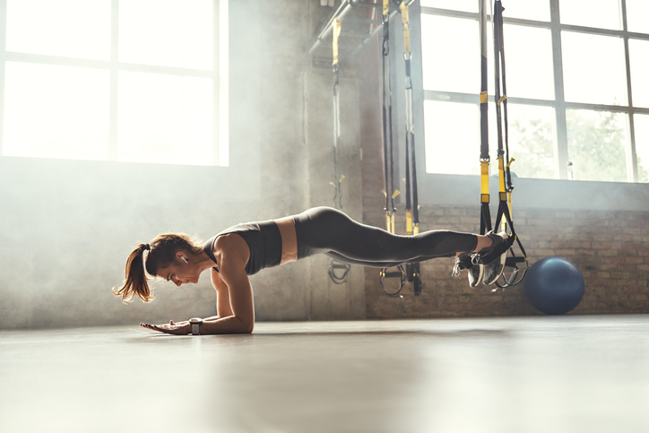 Healthy lifestyle. Young athletic woman doing plank with trx fitness straps in the gym. Professional sport. TRX Training. Workout