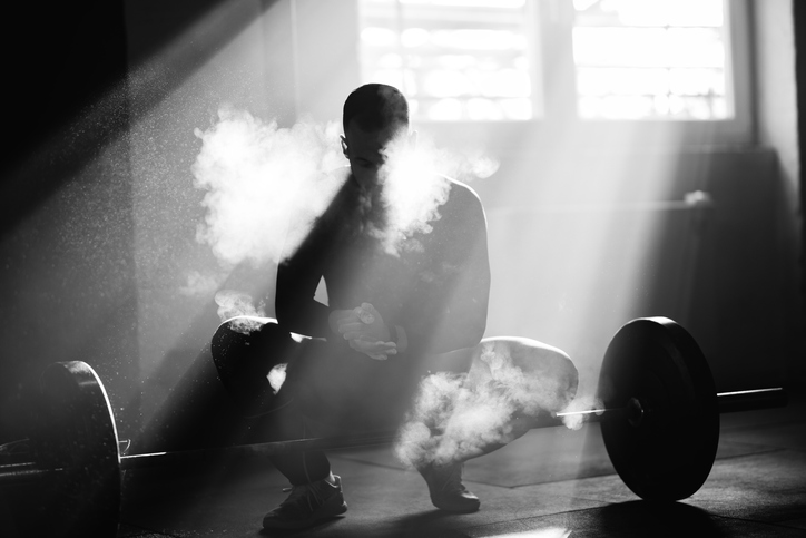 Black and white photo of muscular build man using sports chalk om his hands before exercising with a barbell in a gym.